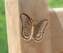 Butterfly crest engraved into one of our teak benches